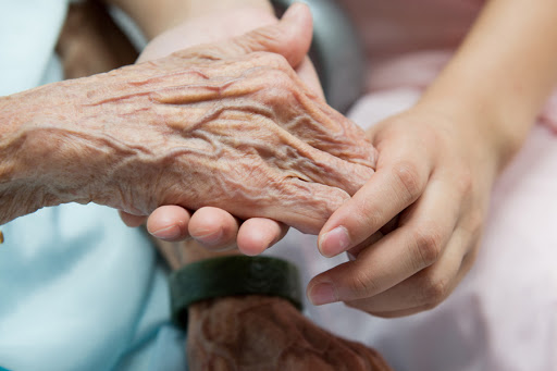 Young girl's hand touches and holds an old woman's wrinkled hands. - it