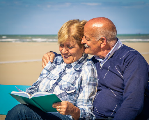 Old happy couple looking at their photo album