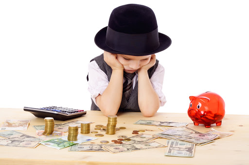 Sad boy in black hat at the table with pile of money - it
