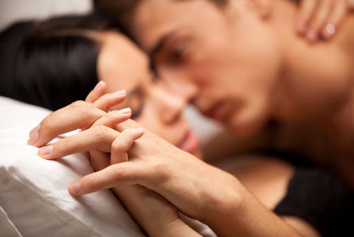 young lovers kissing on the couch. focused on hand - it