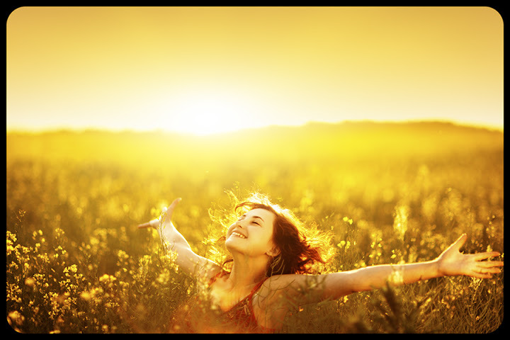 Young happy woman in canola field on sunset