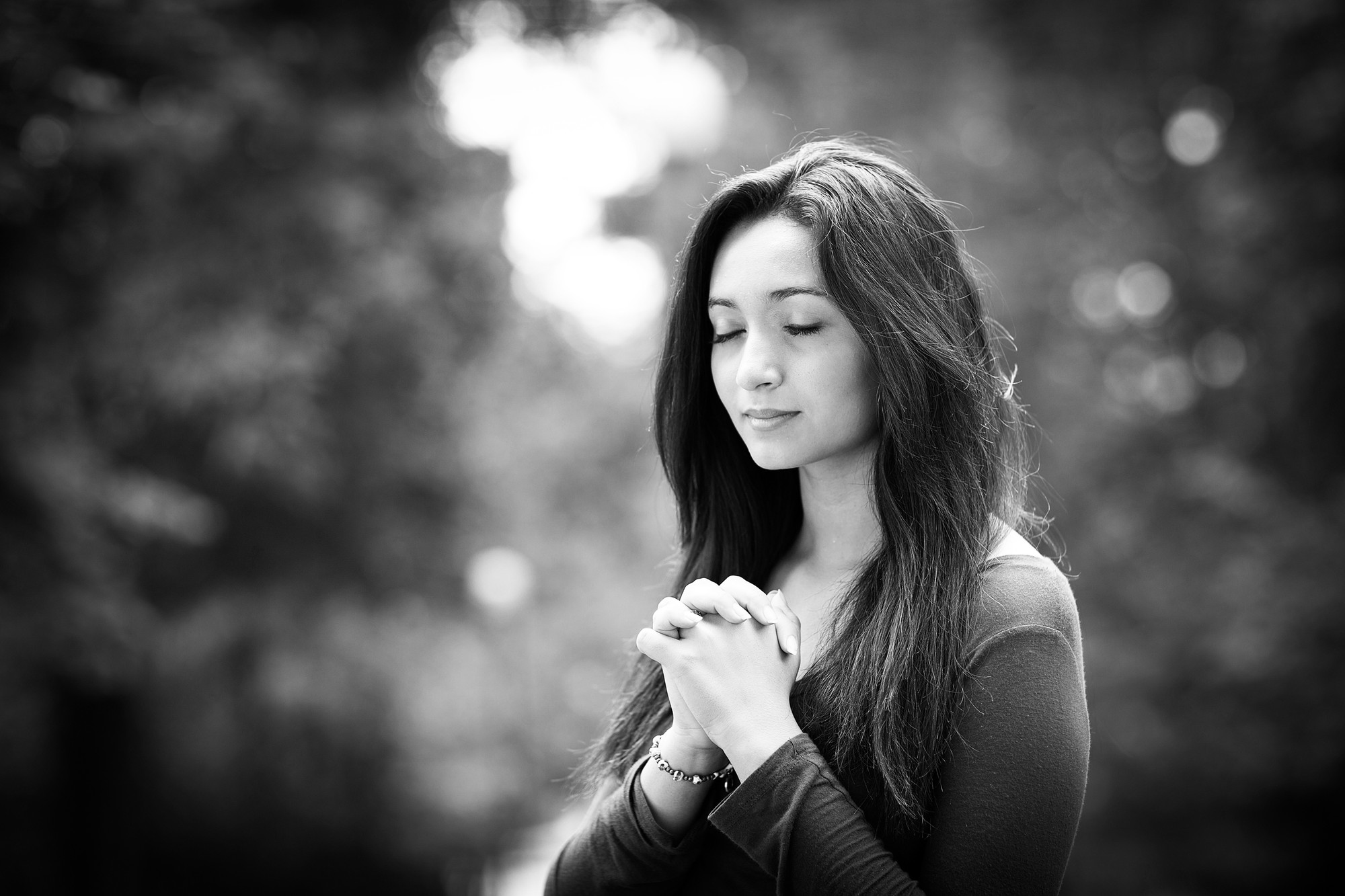Woman hands praying on Outdoors black and white