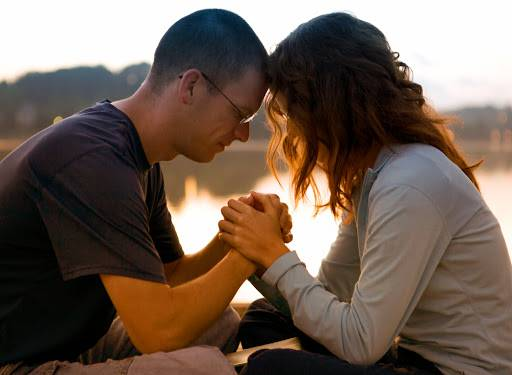 couple praying holding hands