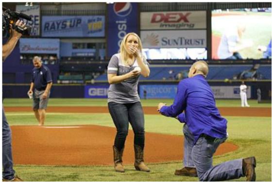 Cameron chiede a Melissa di sposarlo durante una partita di baseball dei Tampa Bay Rays. Mark Loren Designs   Facebook