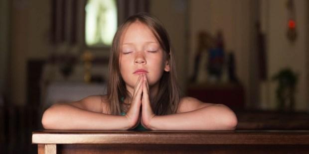 CHILD PRAYING IN PEW
