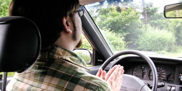 MAN PRAYING IN CAR