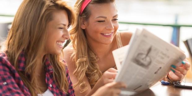 GIRLS READING NEWSPAPER