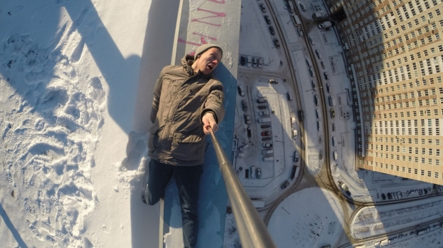 man selfie on edge of roof of tall building