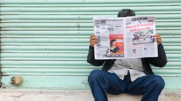 MAN, READING, NEWSPAPER