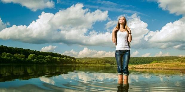 mujer bañando sus pies en un río