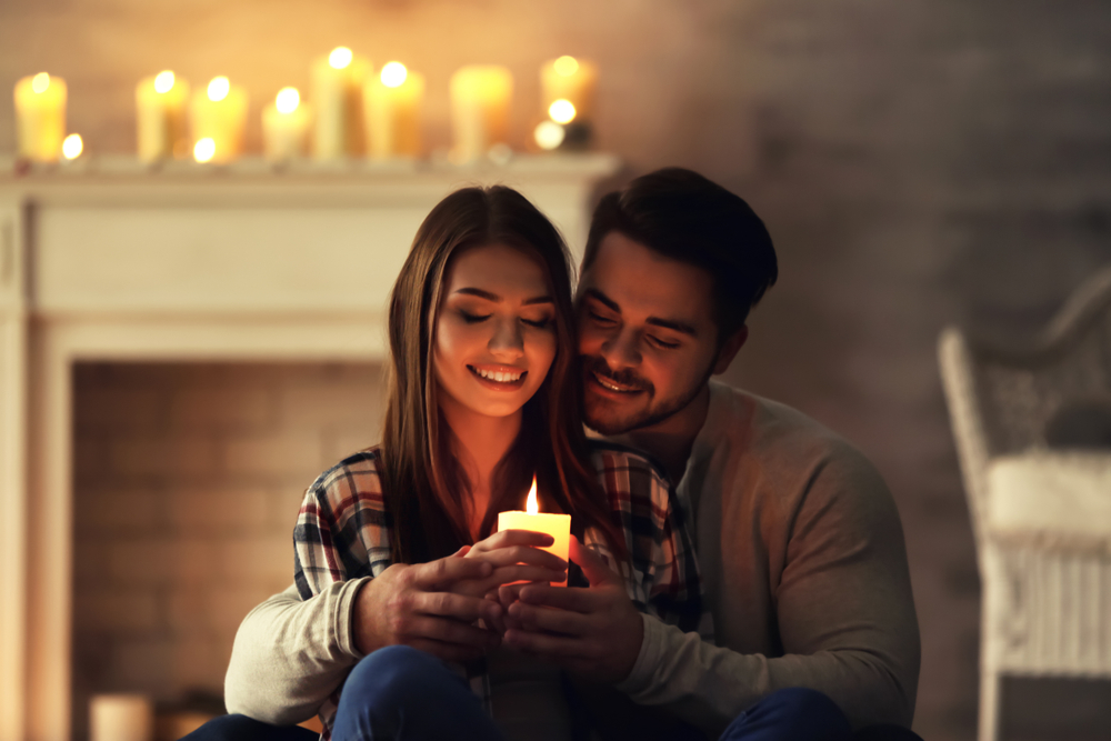 COUPLE AT HOME HOLDING CANDLE