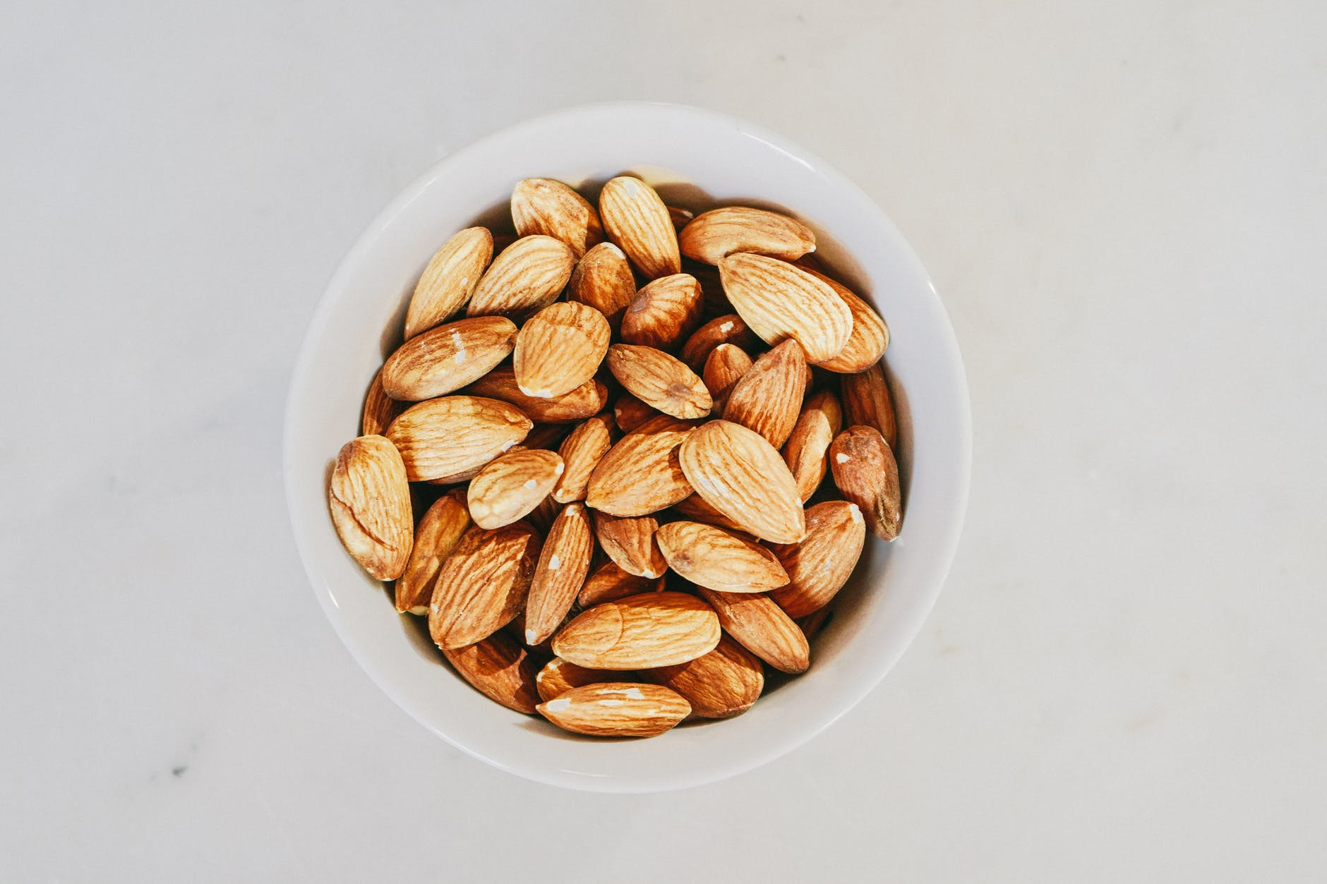 brown almond nuts on white ceramic bowl