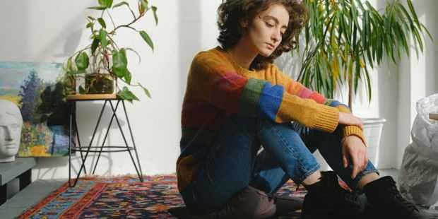 lady sitting near paintings on floor in studio