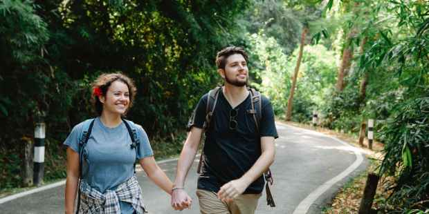 delighted couple holding hands while strolling on road in tropical park