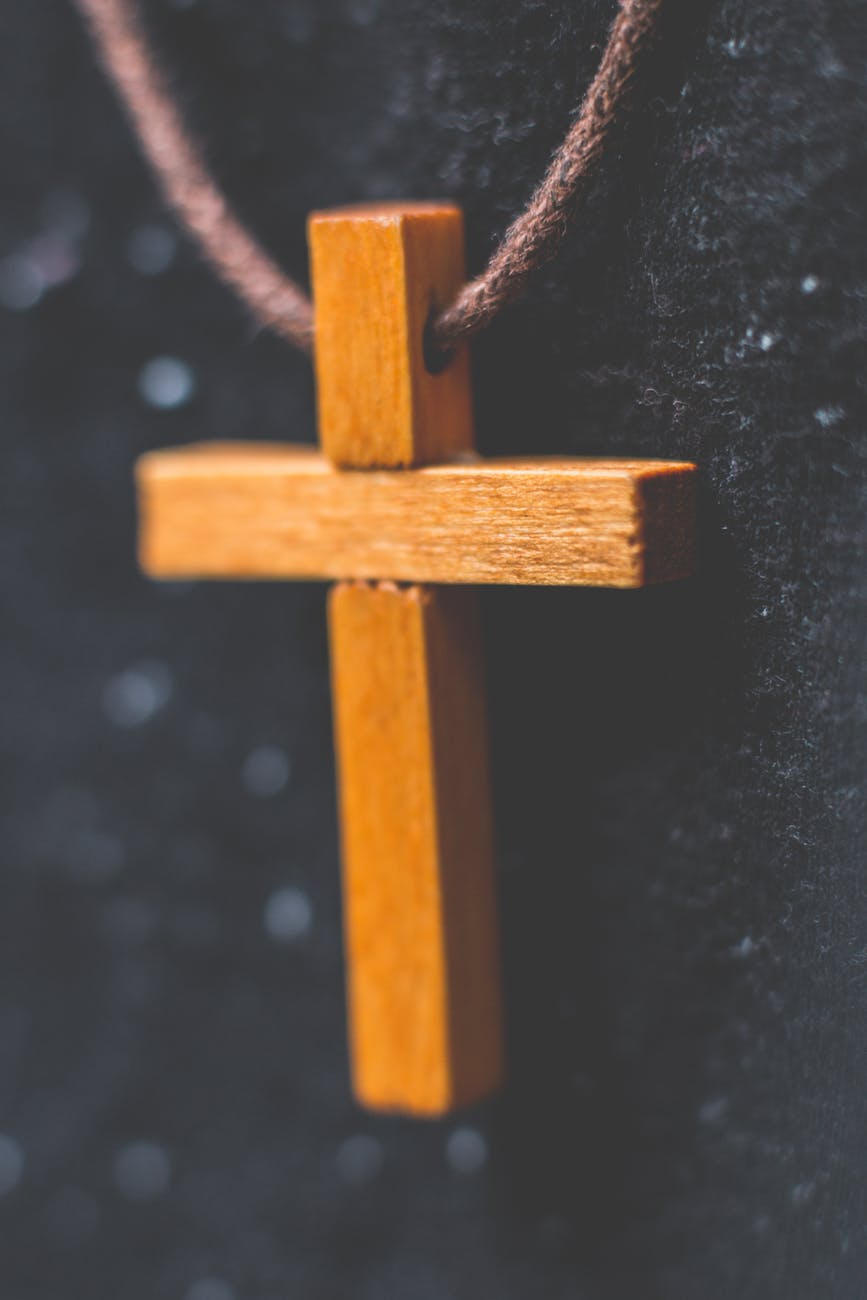 brown wooden cross pendant on closeup photography
