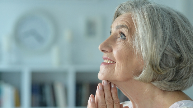 ELDERLY WOMAN PRAYS,